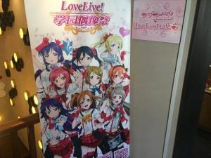 3階入り口の写真。数多の女の子が出迎えてくれます。きちんとLoveLive! Cafeと書いてます!