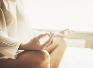 Hands of young beautiful woman practicing yoga at home